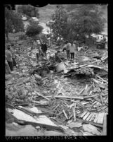 Chavez Ravine property owners looking through bulldozed remains of houses in Los Angeles, Calif., 1959