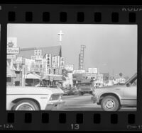 Street lined with storefronts and signs in Chinese and English in San Gabriel, Calif., 1987