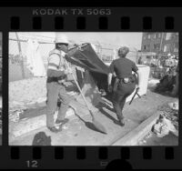 Homeless man being ousted from camper shell on Skid Row in Los Angeles, Calif., 1987