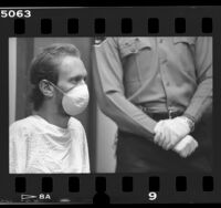 HIV positive Joseph Markowski wearing mask flanked by sheriff wearing latex gloves in court in Los Angeles, Calif., 1987