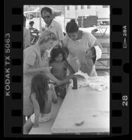 "Nurse Janice Estes attending to toddler with sores at ""Dust Bowl Hilton,"" homeless camp in Los Angeles, Calif., 1987"