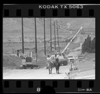 Horseback riders passing workers installing pipelines for development in Palmdale, Calif., 1987