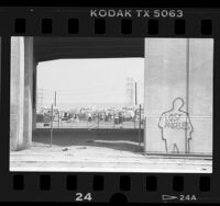 "Outline of human figure with writing ""Lost Angeles"" on column at homeless camp in Los Angeles, Calif., 1987"