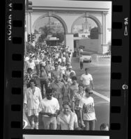 Participants passing gates of Paramount Studio during walk for AIDS Project Los Angeles, 1987