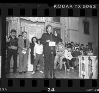Father Richard Estrada [?] with released INS detainees at Our Lady Queen of Angels Church, Calif., 1987