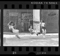 Youngsters on swings at graffiti covered park in South-Central Los Angeles, Calif., 1988