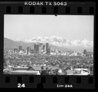 Cityscape of downtown Los Angeles with backdrop of snow covered mountains viewed from Baldwin Hills, Calif., 1988