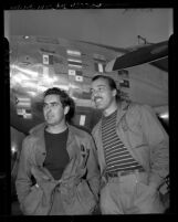 Actors Tyrone Power and Cesar Romero beside Power's plane on return from Latin-American good-will tour, Los Angeles, 1946