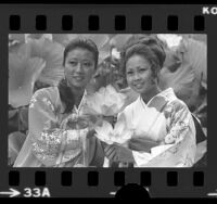 Sung Lee, Miss Korea, and Naomi Dguchi, Miss Nisei posing with lotus flowers at Lotus Festival in Los Angeles, 1975