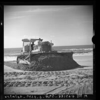Tractor sieving sand along shore at Redondo Beach, Calif., 1975