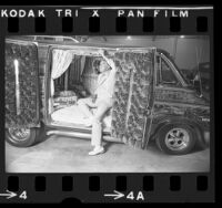Man inspecting the crushed velvet interior of a custom conversion van in Los Angeles, Calif., 1975