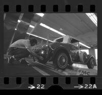 George Adelsperger inspecting Model T Roadster at emission inspection station in Calif., 1975