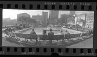 Wide-angle panoramic of people seated on park benches around fountain in Pershing Square, looking south, Los Angeles, Calif., circa 1973