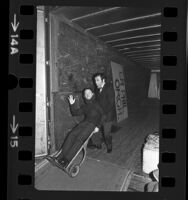 Conductor Zubin Mehta and bassist Dennis Trembly clowning around on loading dock in Los Angeles, Calif., 1975