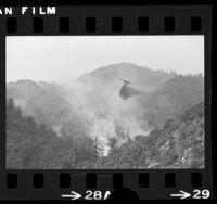 DC-6 airplane dropping fire retardant on wildfire near Mount Baldy Village, Calif., 1975