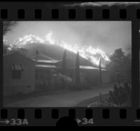 Man watering down roof of house as wildfire burns on hill behind house in Lake View Terrace, Calif., 1975