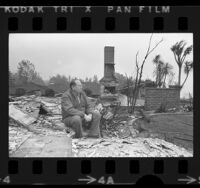 Robert Bray sitting amid remains of home that was destroyed by wildfire in Glendale, Calif., 1975