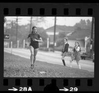 Marathon runner, Jackie Hansen running along median of San Vicente Blvd. in Santa Monica, Calif., 1975