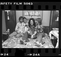 Marty Balin, Grace Slick, and Paul Kantner of Jefferson Starship seated on hotel room bed in Los Angeles, Calif., 1976