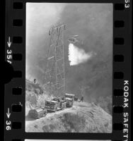 Helicopter dropping water on wildfire as firefighters watch near Porter Ranch, Calif., 1976