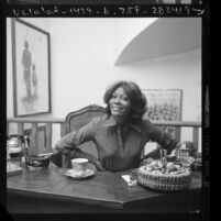 Singer Dionne Warwick seated at desk in Los Angeles, Calif., 1976