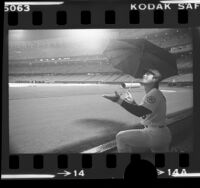 Baseball player Steve Garvey with umbrella, watching rain fall at Dodger Stadium, Los Angeles, 1976