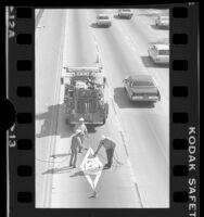 Workers painting diamond on HOV lane, Santa Monica Freeway, Los Angeles, 1976