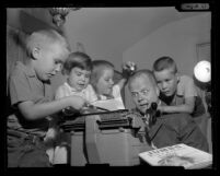 Children's books writer Edmund Lindop at a typewriter with his nieces and nephews crowding around him, 1961
