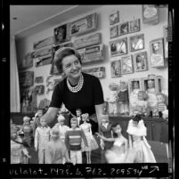 Ruth Handler, executive of Mattel Toy company, posing with collection of Barbie dolls, 1961