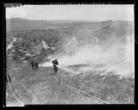 Firemen run up Mt. Washington hill to put down wildfire flames in Los Angeles, Calif., 1961