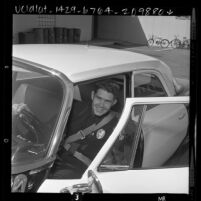 Police officer Paul Lembke showing safety [seat] belt installed in all police cars in Torrance, Calif., 1961