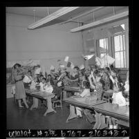 Elena Kunz covering her ears as third graders hurl papers in air on last day of school at Castelar Elementary School in Los Angeles, Calif., 1961