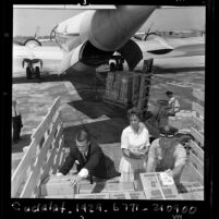 Richard L. Denison, Judy Way and Mark Hessel loading plane for Books for Africa, Calif., 1967