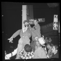 Protesters hanging effigy of Fidel Castro on street sign at Hollywood Blvd. and Vine St., Los Angeles, 1961