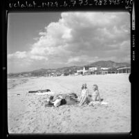 Three people sunbathing on the shoreline of The Malibu Colony, Calif., 1976