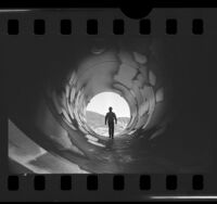 Workman walking through pipe at Castaic Hydroelectric Power Plant, Calif., 1976