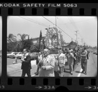 Members of St. Peter's Church carrying Madonna of the Stars in procession down street in Los Angeles, Calif., 1976
