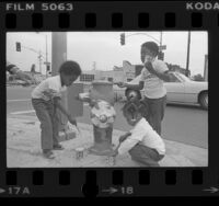 Three African American preschoolers painting fire hydrant for United States Bicentennial in Los Angeles, Calif., 1976