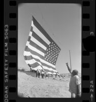 Rancher Bob Older watching unfurling of 67x102 foot American flag for U.S. bicentennial in Oro Grande, Calif., 1976
