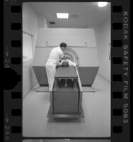 Technologist George Drianis assisting patient during computerized axial tomography (CT) scan at Good Samaritan Hospital, Los Angeles, Calif., 1976