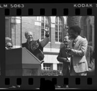 President Gerald Ford on podium with running back Ricky Bell during campaign stop at University of Southern California, 1976