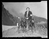 Air Raid warden Pauline McNab with three dogs patrolling Los Flores Canyon during brush fire in Los Angeles, Calif., 1942
