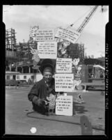 Welder Alfred Barnes displaying safety and morale signage at California Shipbuilding Corp. yard in Terminal Island, Calif., circa 1943