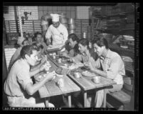 Cook serving food to eight jail trustees in the Los Angeles County Jail kitchen, circa 1943