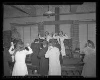 Two women leading prayers at Angelus Temple after news of Aimee Semple McPherson's death