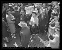"People holding up newspapers with headline ""Hitler Dead  Peace any hour --Churchill"" in Los Angeles, Calif., 1945"