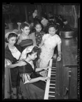 Five women in ethnic costumes at piano during the 1945 Los Angeles Filipino Fiesta