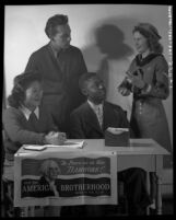 Four youths manning desk during the American Brotherhood Week in 1946,
