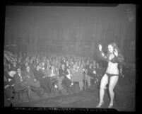 Burlesque dancer Betty Rowland on stage performing before male audience, circa 1946