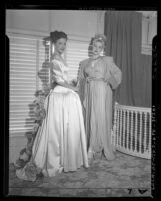 Actress Cathy Downs modeling evening gowns with unidentified woman, circa 1946